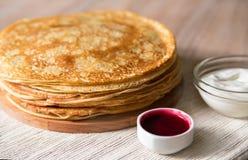Una pila di pancake russi sottili su un bordo di legno, su una salsa della bacca e su una panna acida Fotografia Stock Libera da Diritti