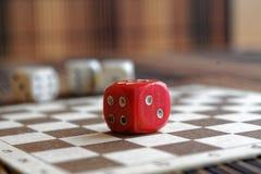 Una pila di plastica di tre bianchi taglia ed un dado rosso sul fondo marrone del bordo di legno Sei cubi dei lati con i punti ne Fotografie Stock