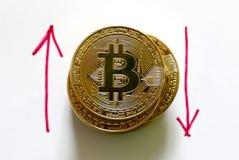 Una pila di replica dorata del bitcoin su Libro Bianco scritto con la freccia rossa su e giù Concetto di finanza e di affari Fotografia Stock Libera da Diritti
