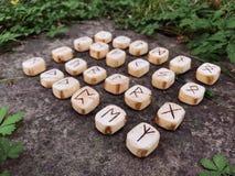 Una pila di rune di legno alle rune di legno della foresta si trova su un fondo della roccia nell'erba verde Le rune sono tagliat fotografie stock libere da diritti