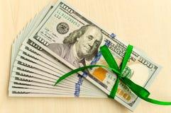 Una pila di soldi con un nastro Regalo costoso Immagine Stock