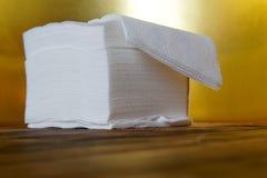 Una pila di tovaglioli di carta igroscopici su un fondo dorato e su una superficie di legno fotografia stock libera da diritti