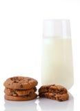 Una pila di tre biscotti di pepita di cioccolato casalinghi, metà dei biscotti e bicchiere di latte Fotografie Stock Libere da Diritti