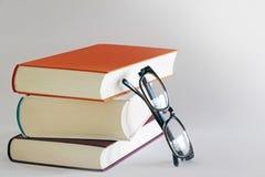 Una pila di tre libri con i vetri di lettura Fotografia Stock