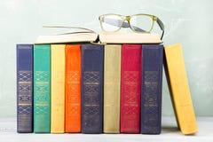 Una pila di vecchi libri e vetri di colore su una tavola Immagini Stock