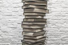 Una pila di vecchi libri sui precedenti del muro di mattoni Fotografie Stock