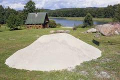 Una pila grande de arena limpia blanca del río miente en un césped cerca de FO Fotografía de archivo