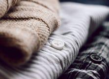 Una pila ordinata di vestiti - una sciarpa beige e due camice immagine stock
