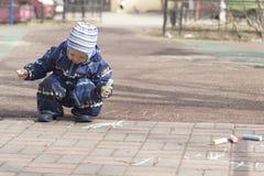 Una pintura de 2 años del muchacho con tiza al aire libre Imagenes de archivo