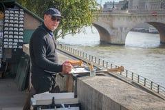 Una pintura del artista del hombre por el río Sena imagen de archivo