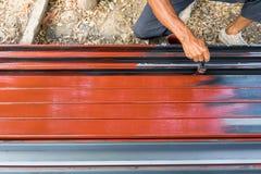 Una pintura del trabajador a prueba de herrumbre en los polos de acero para la construcción imagen de archivo libre de regalías