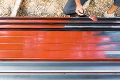 Una pintura del trabajador a prueba de herrumbre en los polos de acero para la construcci?n imagenes de archivo