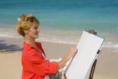 Una pintura femenina del artista en la playa imagenes de archivo