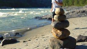 Una pirámide de piedras se coloca en la orilla del río metrajes