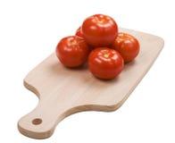 Una piramide dei cinque pomodori sulla scheda di taglio Fotografie Stock