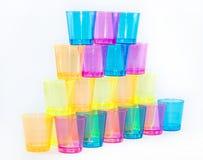 Una piramide delle tazze colorate su un fondo bianco - giallo, arancio, rosa e blu Fotografia Stock Libera da Diritti
