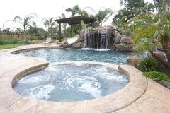 Una piscina con una cascada en un patio trasero de lujo Imagen de archivo