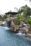Una piscina con una cascada en un patio trasero de lujo Fotografía de archivo libre de regalías