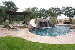 Una piscina con una cascada en un patio trasero de lujo Imagenes de archivo