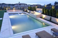 Una piscina con una cascada en un patio trasero de lujo Fotos de archivo