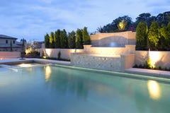 Una piscina con una cascada en un patio trasero de lujo Imagen de archivo libre de regalías