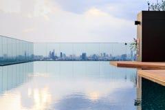 Una piscina en el tejado con el fondo de la ciudad Foto de archivo libre de regalías