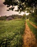 Una pista de suciedad rural y un granero americano Fotos de archivo libres de regalías
