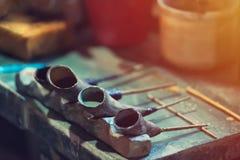 Una pittura ceramica del decoratore delle terraglie foggia in pieno di pittura Strumenti d'annata, sguardo d'annata fotografia stock libera da diritti