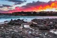 Una pittura delle nuvole brucianti ed il mare e le rocce immagine stock