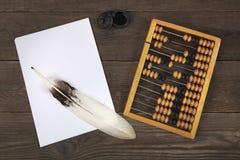 Una piuma d'oca si trova su un mucchio dei fogli di carta bianchi I vecchi conti e un retro calamaio sono situati parallelamente  Fotografia Stock Libera da Diritti