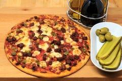 Una pizza del banquete de la carne con la salmuera y las aceitunas como lado Fotografía de archivo