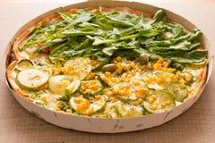 Una pizza di due sapori: Rucola e zucchini con i noccioli di cereale dettaglio Immagini Stock