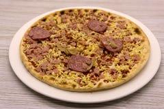 Una pizza di merguez congelata su un tagliere di legno fotografia stock libera da diritti