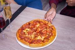 Una pizza en una tabla fotos de archivo