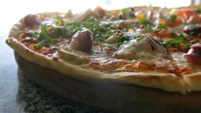 Una pizza recientemente cocida grande con la cual hay vapor, una visi?n cercana Pizza deliciosa con el tomate, verdes, b?varos almacen de metraje de vídeo