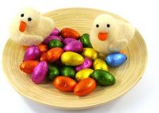 Una placa aislada del bambú con los huevos y los anadones de Pascua Foto de archivo libre de regalías