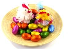 Una placa aislada del bambú con los huevos y los pollos de Pascua Imagen de archivo