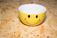 Una placa con una sonrisa de la imagen, en una tabla de madera Foto de archivo