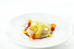 una placa de conchas de peregrino, los tomates y el resorte se mezclan Imagen de archivo