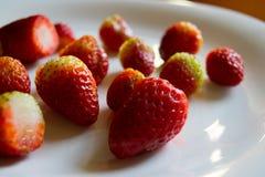 Una placa de fresas orgánicas tajadas foto de archivo