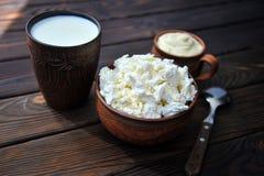 Una placa de la arcilla con requesón, una taza de arcilla con crema agria, una taza con leche y una cuchara en tablen imágenes de archivo libres de regalías