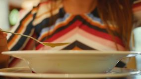 Una placa de la comida La chica joven come la sopa con una cuchara en un café Ci?rrese encima de tiro almacen de metraje de vídeo