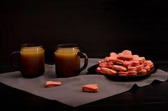 Una placa de las galletas con en forma de corazón rojo, tazas de café con la leche, el día de tarjeta del día de San Valentín Fotografía de archivo