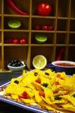 Una placa de los nachos deliciosos de la tortilla con la salsa de queso derretida, c Fotografía de archivo