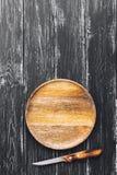 Una placa de madera vacía con un cuchillo en una superficie de madera negra Fotografía de archivo libre de regalías