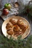Una placa de oro de las bolas de masa hervida de manzana con los palillos de canela y los apoyos rústicos Imagen de archivo libre de regalías