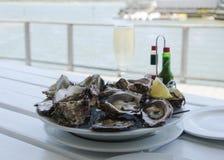 Una placa de ostras abiertas frescas y de un vidrio de champán en una tabla blanca con vistas al océano, foco selectivo Imagen de archivo libre de regalías