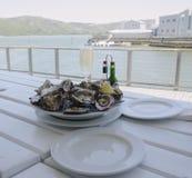 Una placa de ostras abiertas frescas y de un vidrio de champán en una tabla blanca con vistas al océano, foco selectivo Imágenes de archivo libres de regalías