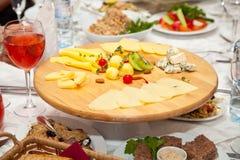 Una placa de quesos y de ensaladas en la tabla del día de fiesta Imagen de archivo
