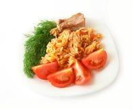 Una placa del alimento - pastas con el tomate y el eneldo. Aislador Fotos de archivo